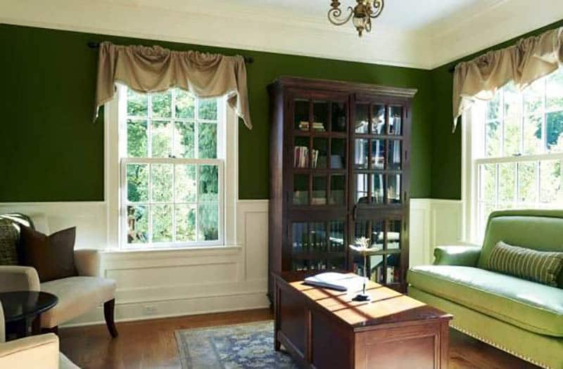 Traditional living room with white wainscoting and dark green paint