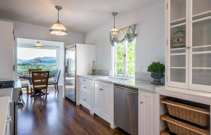 Traditional white cabinet galley kitchen with teak wood flooring