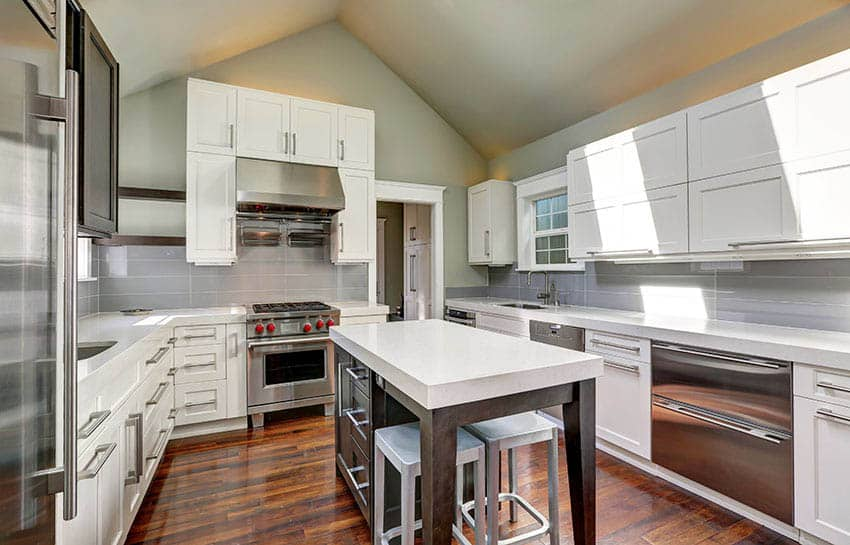 White kitchen with gray backsplash white counters island and silver hardware