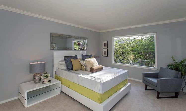 Contemporary bedroom with gray painted walls and contrasting yellow bottom bed sheet