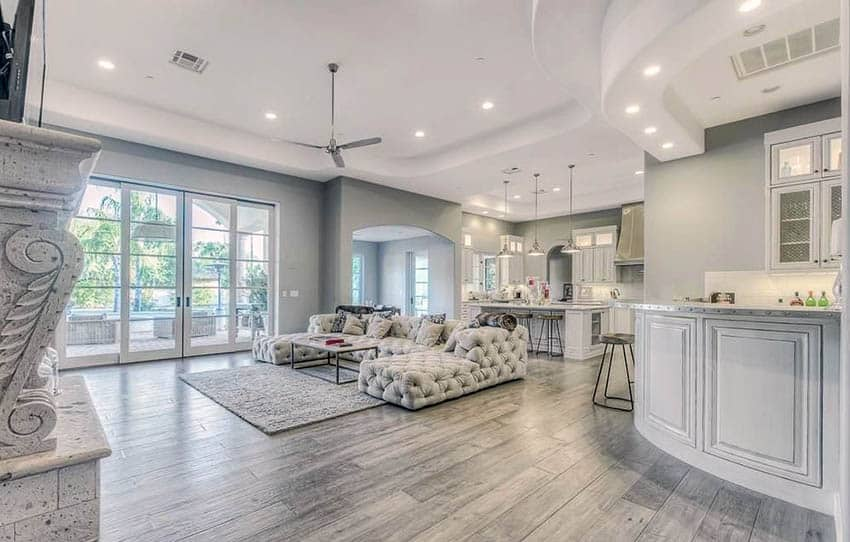 Contemporary living room with corner home bar with white cabinets and bleached wood flooring
