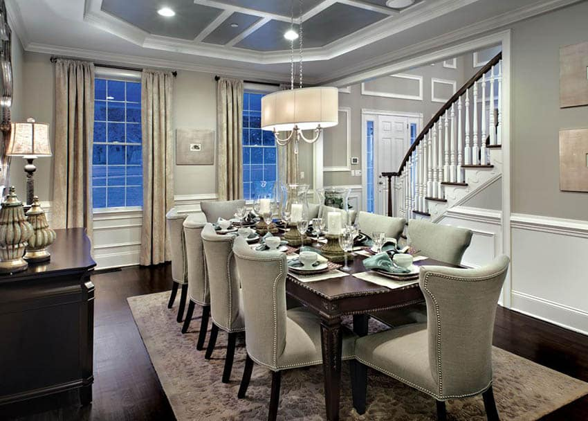 Dining room with warm lighting linen shade chandelier, table lamp and recessed lights