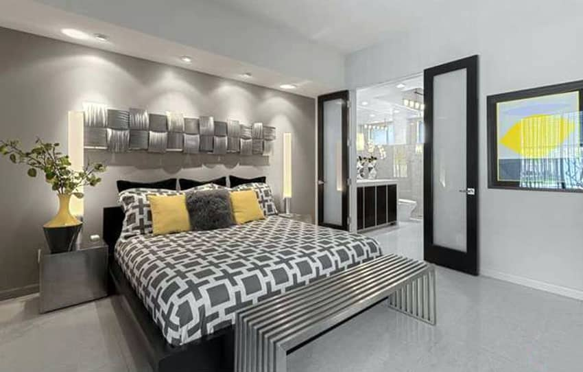 Gray modern master bedroom with metal ottoman and yellow decor