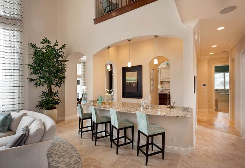 Home bar with limestone floors and pendant lights