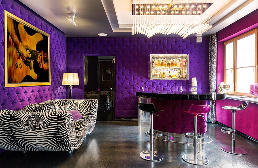 Living room with tufted purple walls zebra couch and modern tufted home bar