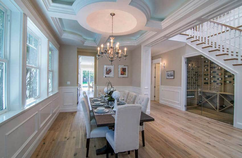 Traditional dining room with chandelier, beige paint and white wainscoting