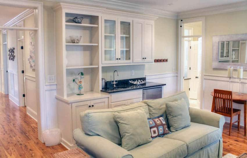 Traditional living room with built in home bar with white cabinet sink and refrigerator