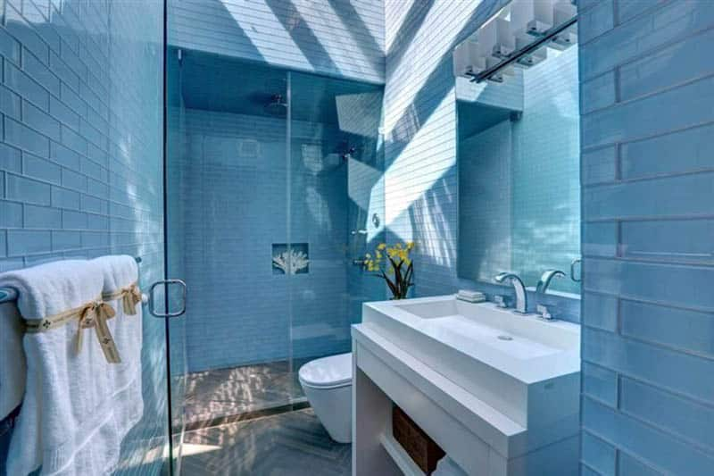 Bathroom with blue glass subway tile and white vanity