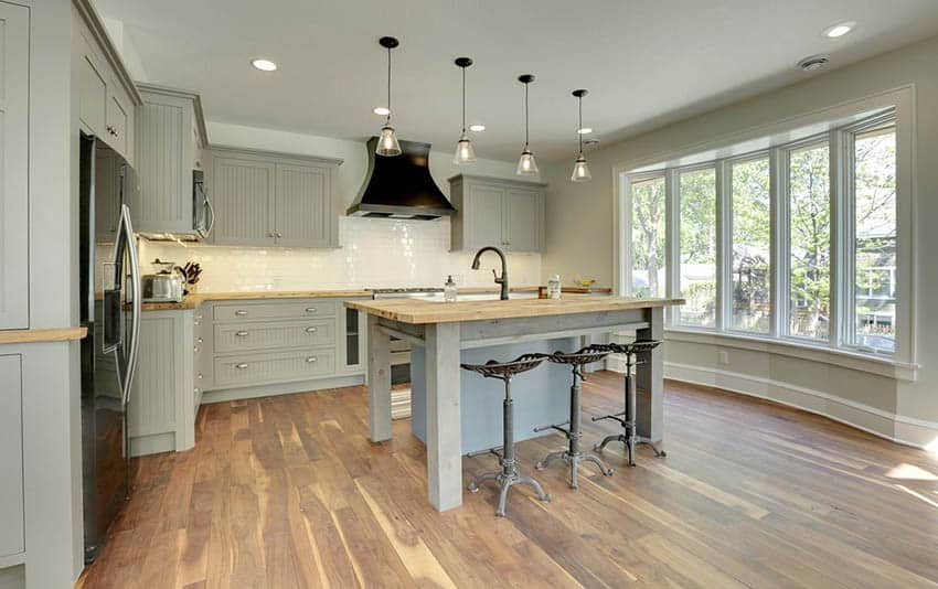Contemporary kitchen with gray cabinets and light gray painted walls with rustic wood countertop island