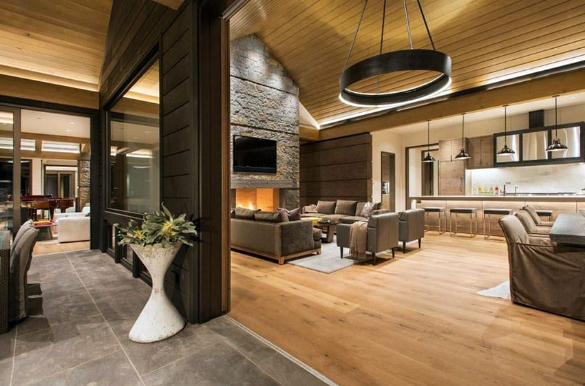 Contemporary living room with drum pendant light wood floors and stone fireplace