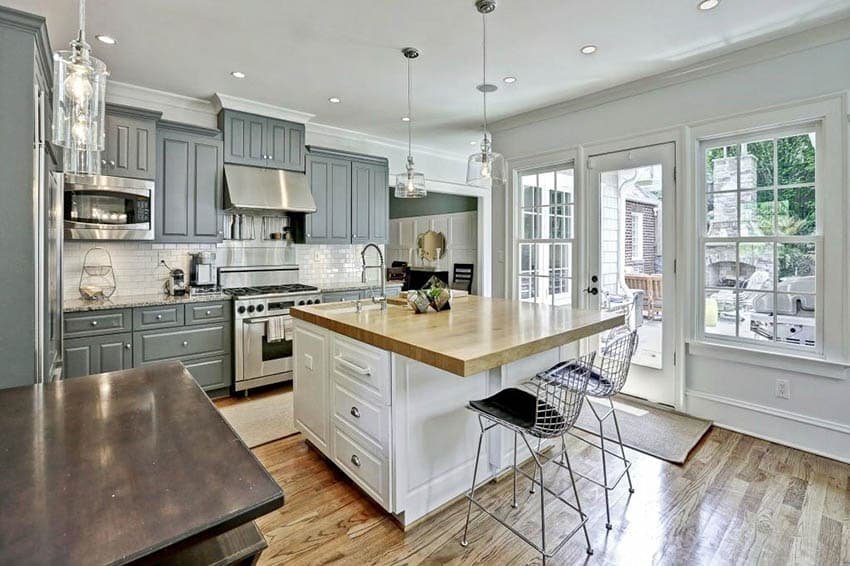 Contrasting kitchen with gray cabinets and white island with butcher block countertop
