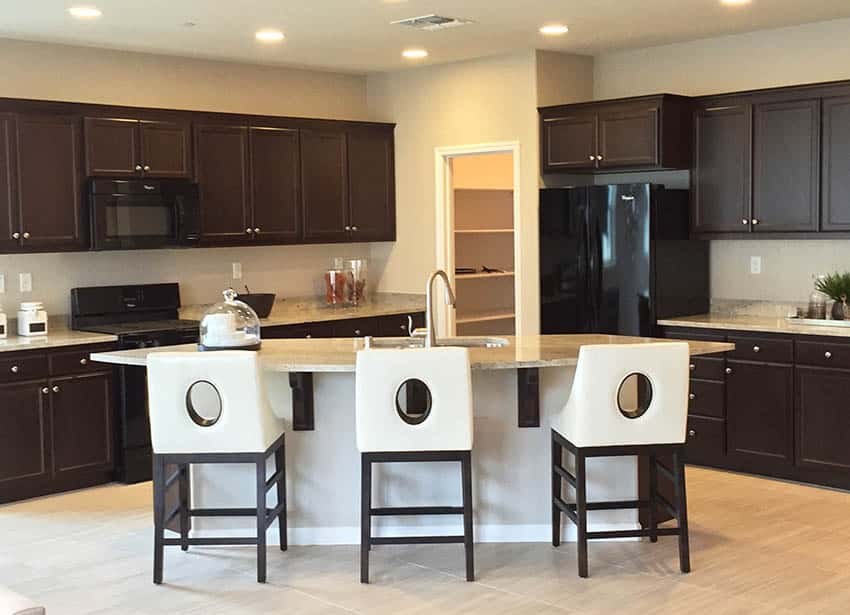 Dark cabinet kitchen with beige color walls and light color granite countertop