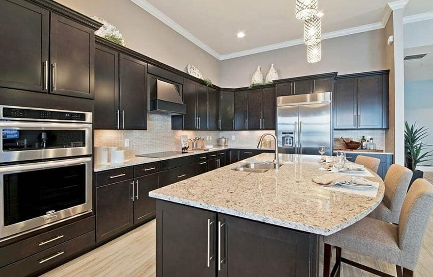 Kitchen with dark cabinets and light gray paint color walls with beige granite counters