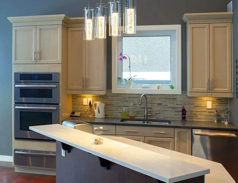 Kitchen with light wood cabinets and dark blue painted walls with island and white solid surface countertop