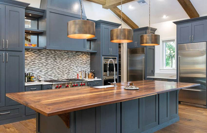 Kitchen with navy painted cabinets wood countertop island and mosaic tile backsplash