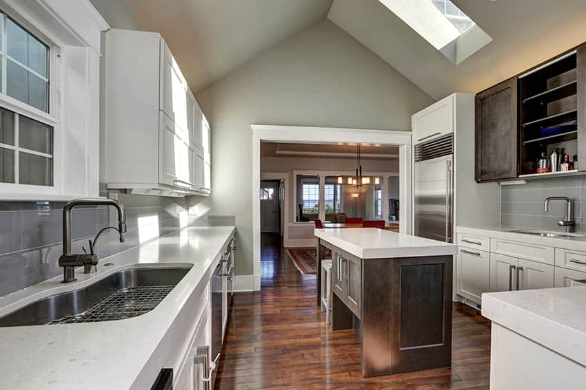 Kitchen with vaulted ceiling greige paint color and white cabinets with quartz countertops
