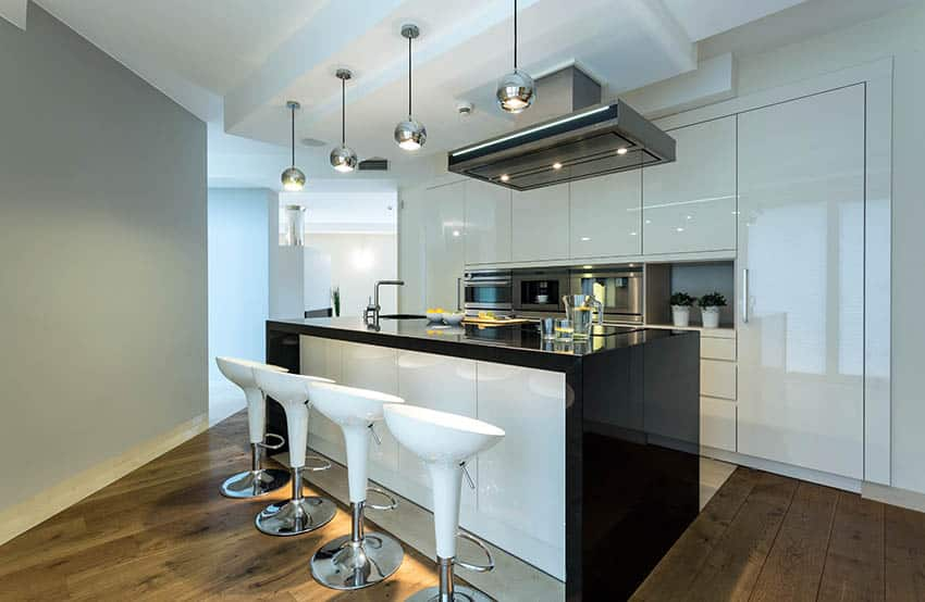 Modern kitchen with white high gloss cabinets and gray painted wall with black counters and dark wood flooring