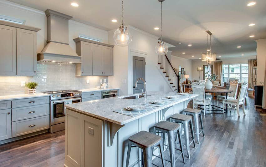 Open concept kitchen with white paint gray cabinets and gray marble counter
