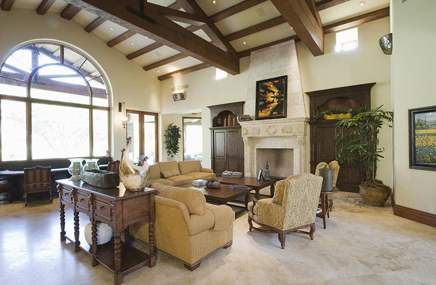 Rustic living room with vaulted ceiling, arched window and stone fireplace