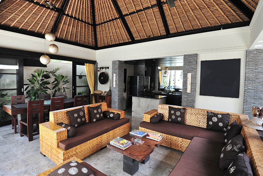 Rustic tropical themed living room with bamboo ceiling and open kitchen