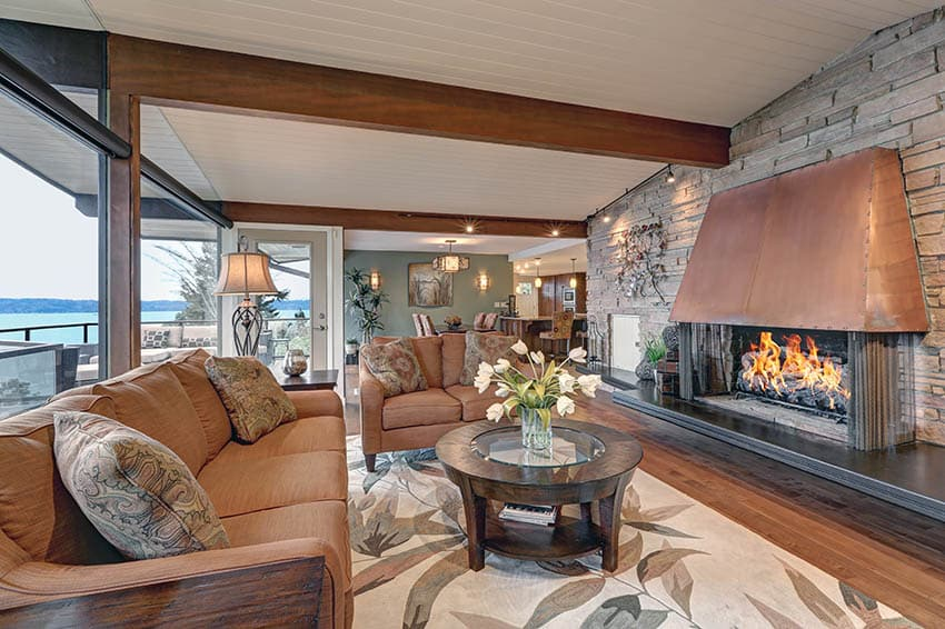 Rustic waterfront living room with large copper fireplace, rock accent wall and wood beams