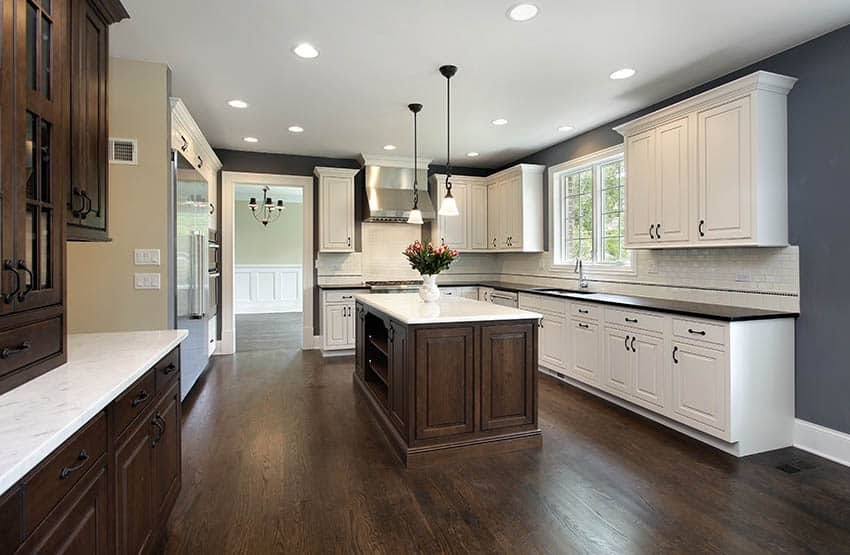 Traditional kitchen with dark gray and tan two tone wall paint and white and brown cabinets