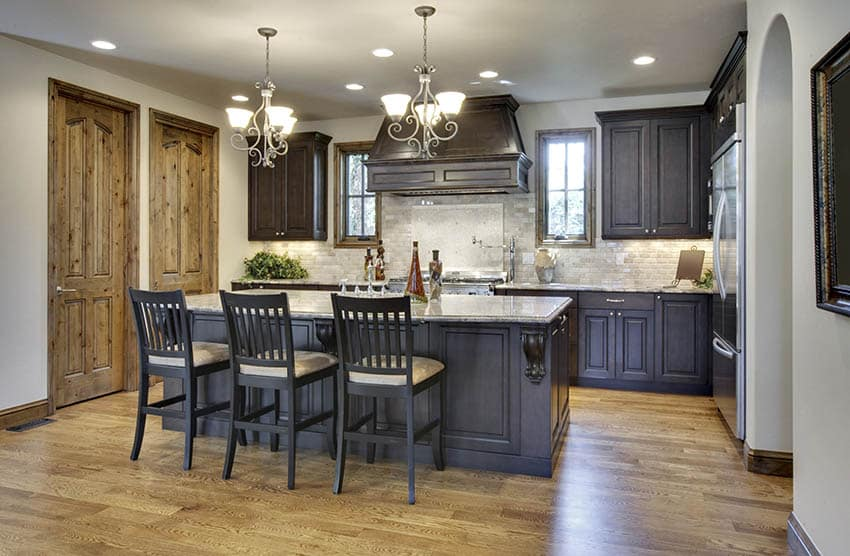 Traditional dark cabinet kitchen with off white wall paint color, beige tile backsplash and wood flooring