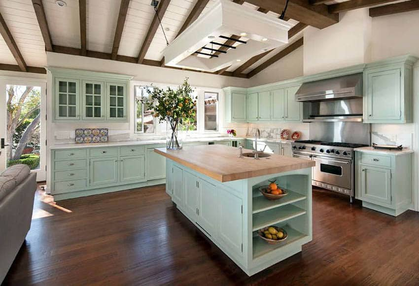 Traditional kitchen with mint green cabinets white countertops with butcher block island