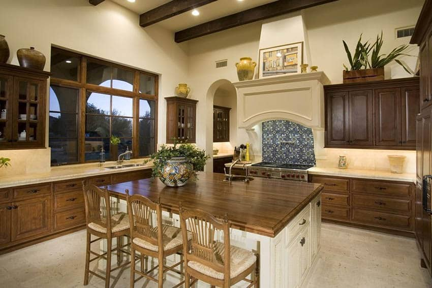 Traditional kitchen with stained wood raised cabinets, cream yellow painted walls and butcher block dining island