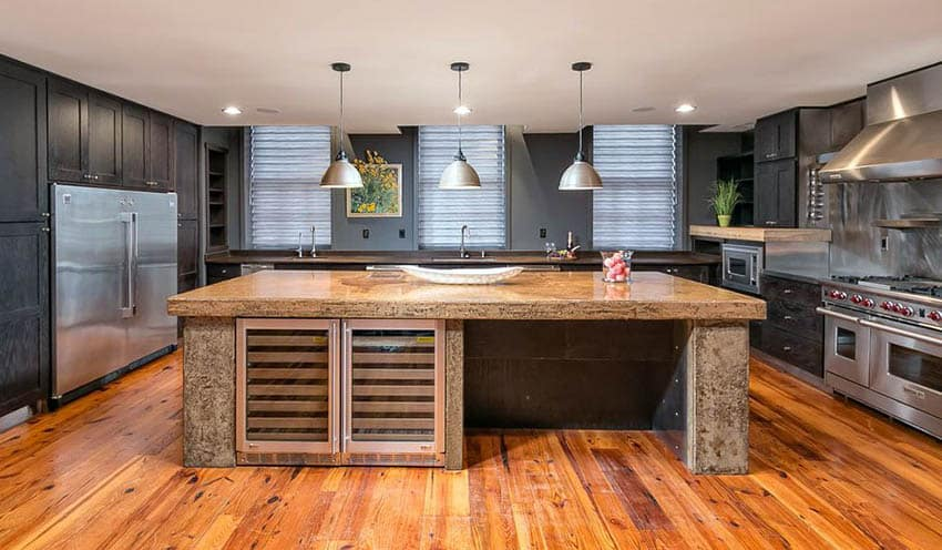Transitional kitchen with black cabinets and deep tone paint color with wood flooring