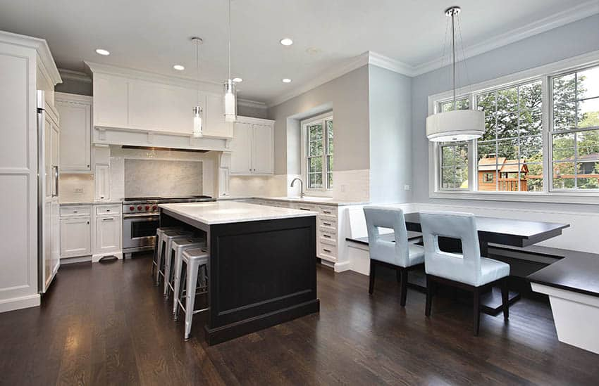 Transitional kitchen with white cabinets, light gray painted walls, dark wood island and marble counters