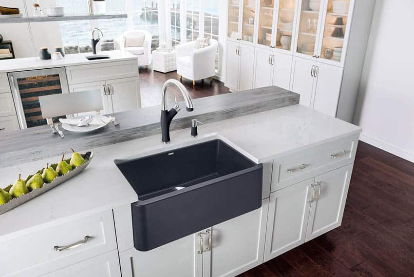 Granite composite kitchen sink with white cabinets and marble countertops