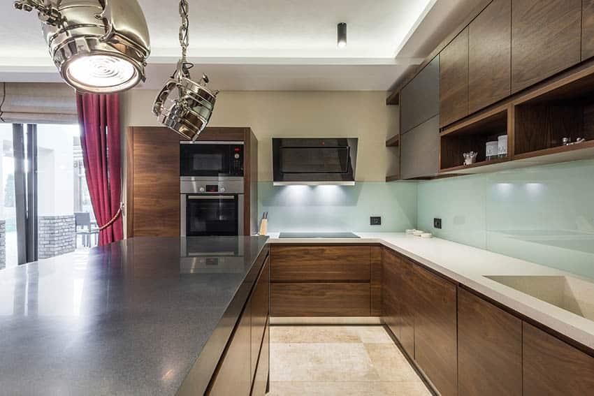Kitchen with european flat panel cabinets with no hardware and aqua blue glass backsplash