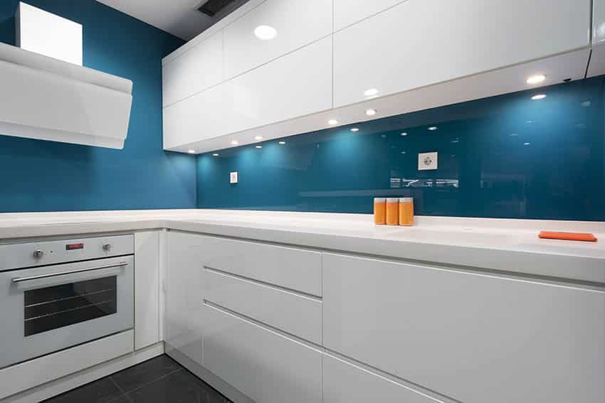 L shaped modern kitchen with white cabinets and dark blue glass backsplash