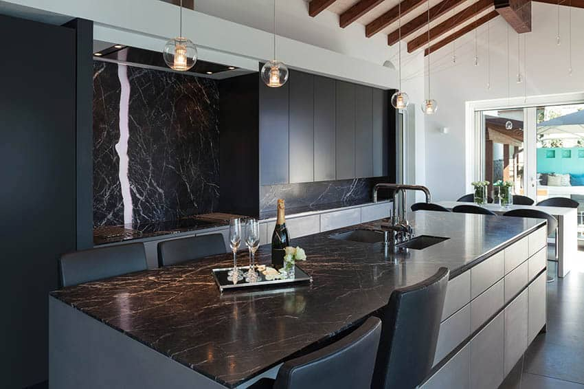 Modern kitchen with black sinks built in island with black marble counter