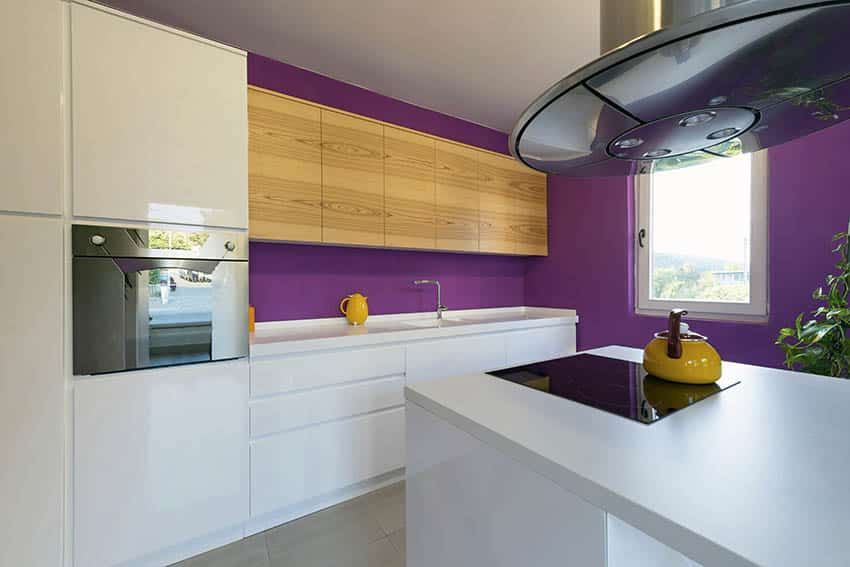 Modern kitchen with white cabinets purple paint color and small island