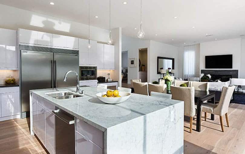Modern kitchen with white high gloss cabinets and waterfall marble island