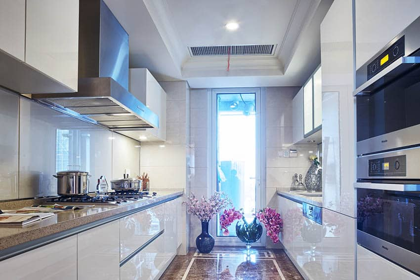 Small modern galley kitchen with high gloss white cabinets and marble floors