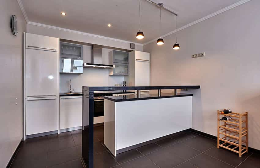 Small modern kitchen with white cabinets black breakfast bar and tile floor