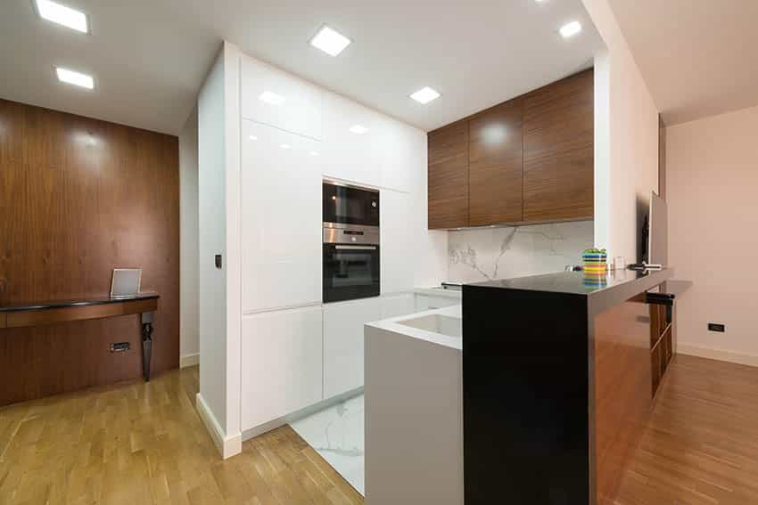 Small modern kitchen with white high gloss cabinets and black countertop