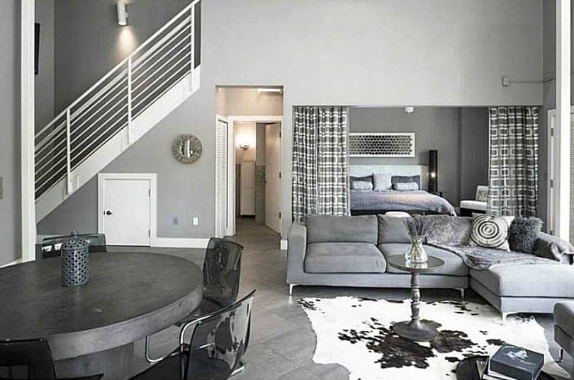 Gray painted living room with bedroom behind curtain