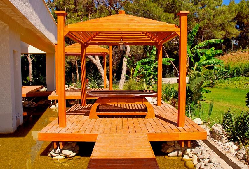 Backyard retreat with pergola deck above garden pond
