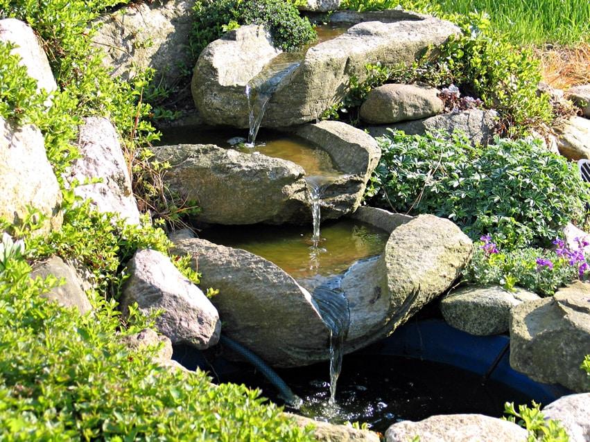 Small stone stream waterfall in garden
