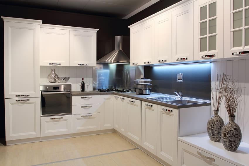 Modern corner kitchen with white cabinetry with chrome hardware