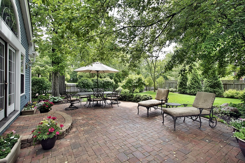 Beautiful brick patio green trees umbrella