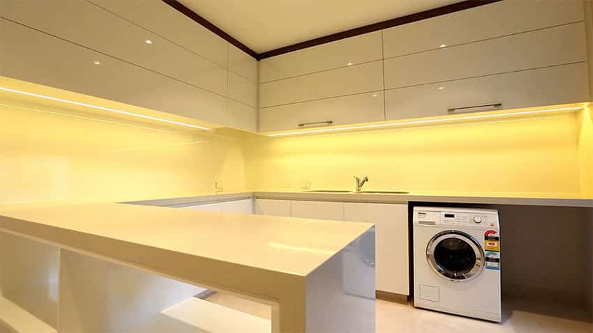 Modern basement laundry room with high gloss white lacquer cabinets