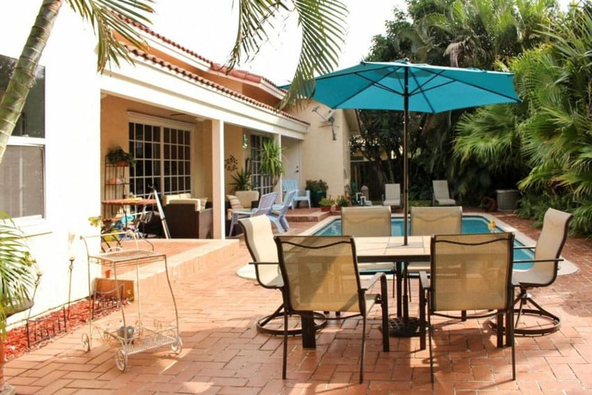 Poolside paver patio with outdoor table and umbrella