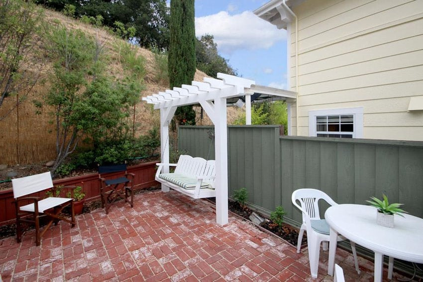 Terracotta patio with swing and outdoor dining table