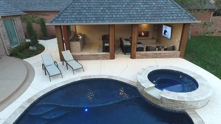 backyard cabana with kitchen, fireplace, tv, pool and spa