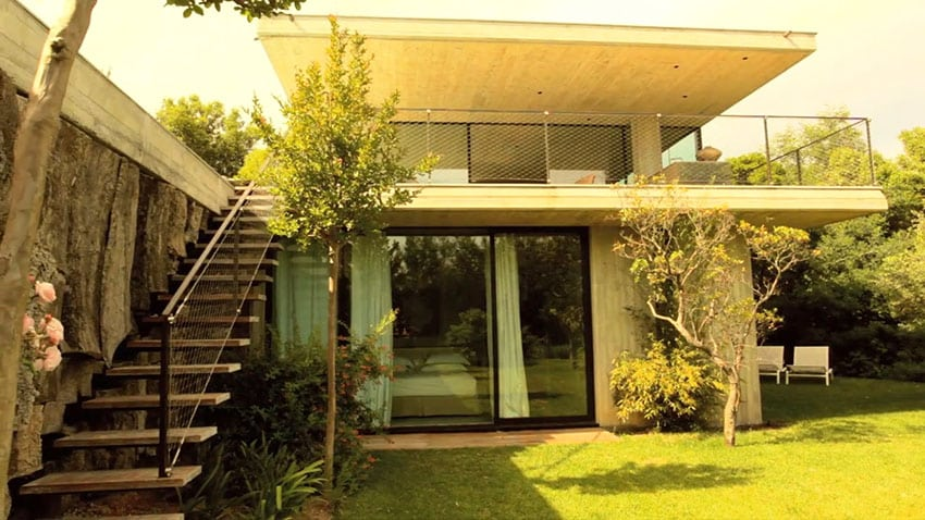 Modern concrete and glass house with top floor balcony and terrace